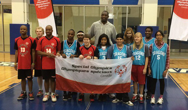 Dikembe Mutombo (centre) poses at Ryerson with young basketball players representing Special Olympics Canada. (Dan Berlin/Ryersonian Staff)