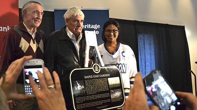 Maple Leafs alumni Bob Nevin, left, and Terry Clancy, centre, join Rams women's hockey team's Janella Brodett to unveil the Heritage Toronto plaque awarded to Ryerson and Loblaw Companies Ltd. (Bruce Laregina / Ryersonian Staff)
