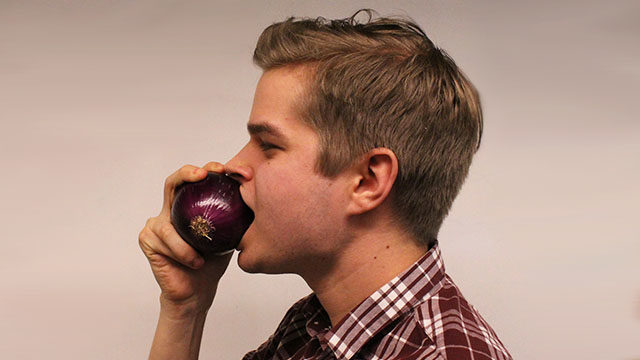 Liam Scott demonstrates how a raw onion can keep you healthy. (Rebecca Sedore / Ryersonian Staff)
