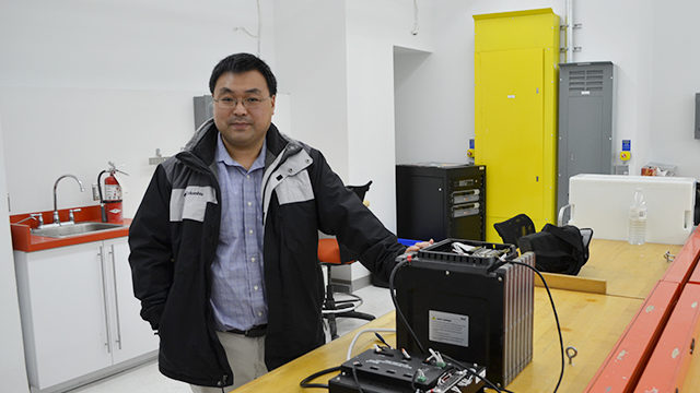 David Xu, Ryerson engineering professor, and the small lithium polymer battery he is testing on. (Peter Lozinski / Ryersonian Staff)