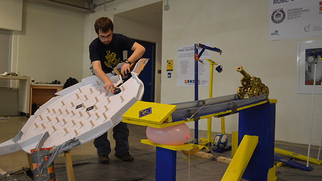 Project leader Derek Stanley makes last minute changes to the Rube Goldberg machine, which was unveiled on March 18.  (Peter Lozinski / Ryersonian Staff)