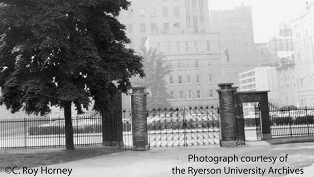 South gates to original campus on Gould Street. The parking lot is now Lake Devo, and O'Keefe Breweries Head Office seen in the distance is now Heaslip House (August 1961). (Courtesy Ryerson University Archives)