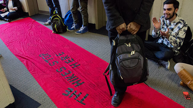 "Lawrence, along with 13 other RSU members and students, protested the tuition increase by laying out a ""red carpet of student debt,"" a red cloth with the title ""Hikes Stop Here,"" outside the room before the meeting began. (Matt Oxman / Ryersonian staff)"