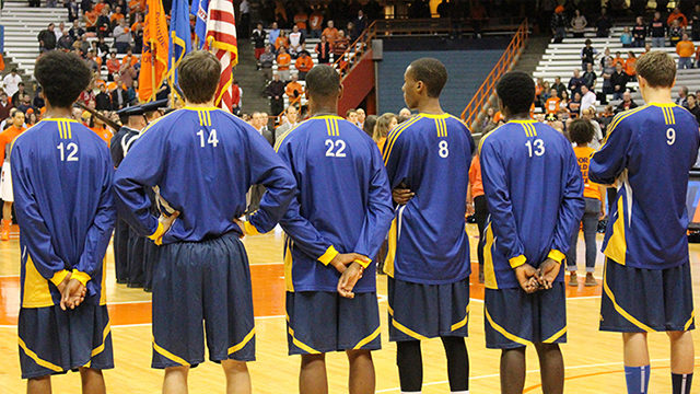 Rams players stand for the National anthem in Syracuse, NY. (Greg DeClara/ Ryersonian File Photo)