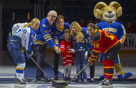 Rams captain Jessica Hartwick, university president Sheldon Levy, Olympian Natalie Spooner, Wickenheiser, Eggy, Gryphons captain Kaitlyn Mora and two young children are at centre ice for the ceremonial puck drop. (Beth Bowers/Ryersonian)