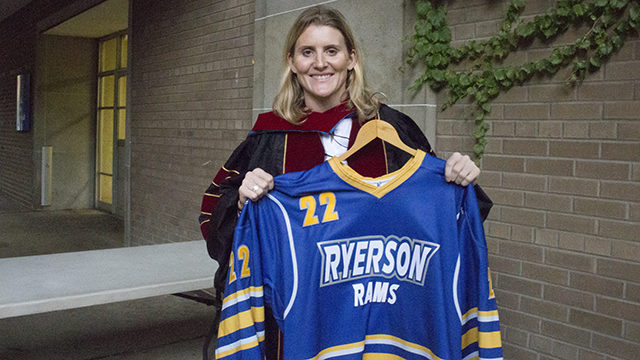 Hayley Wickenheiser holds up the jersey Ryerson presented her as an honorary doctorate. (David Chen/Ryersonian)