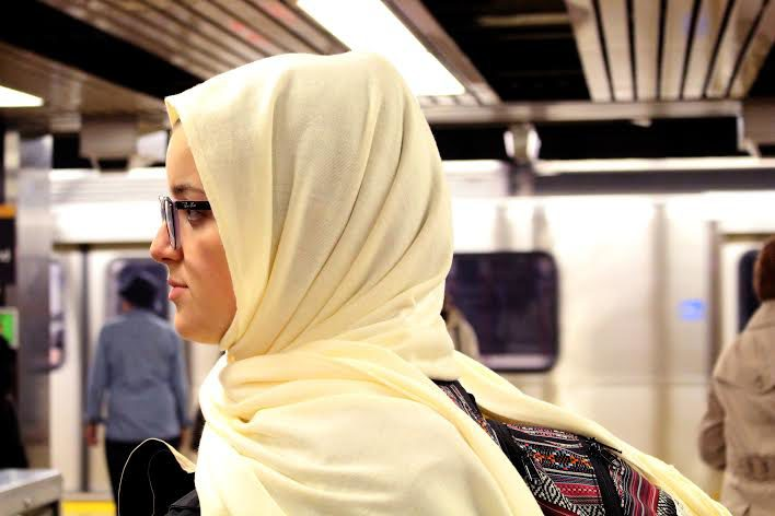 Mariam waits for the subway wearing her hijab