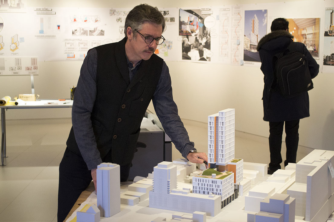 Lead designer from Perkins + Will, Andrew Fontini, surveys one of the models at Public Space Rules, a show on display in the architecture building.