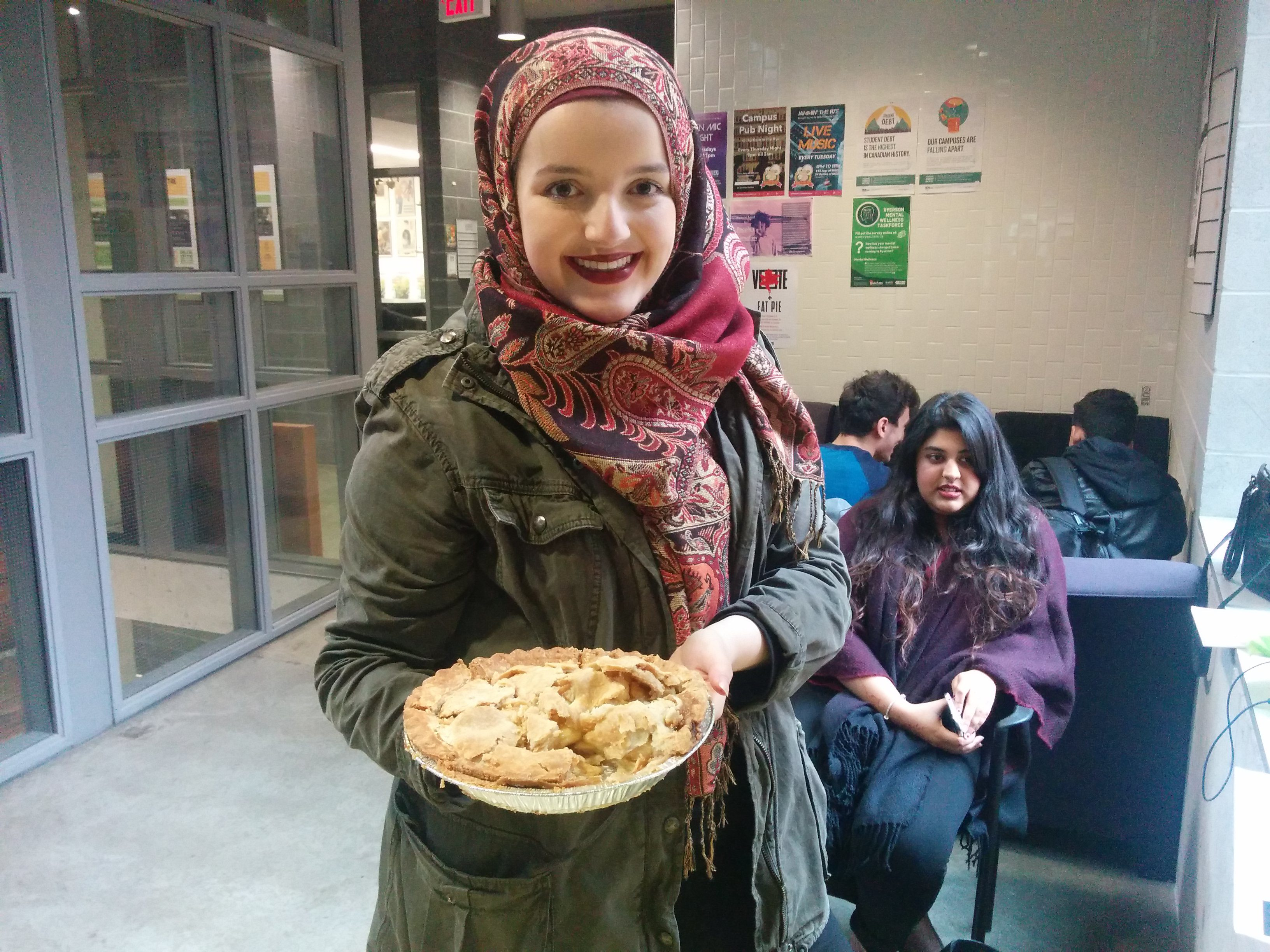 Mariam Nouser holds up a pie just across from the polls in the SCC (Arthur White/Ryersonian Staff).