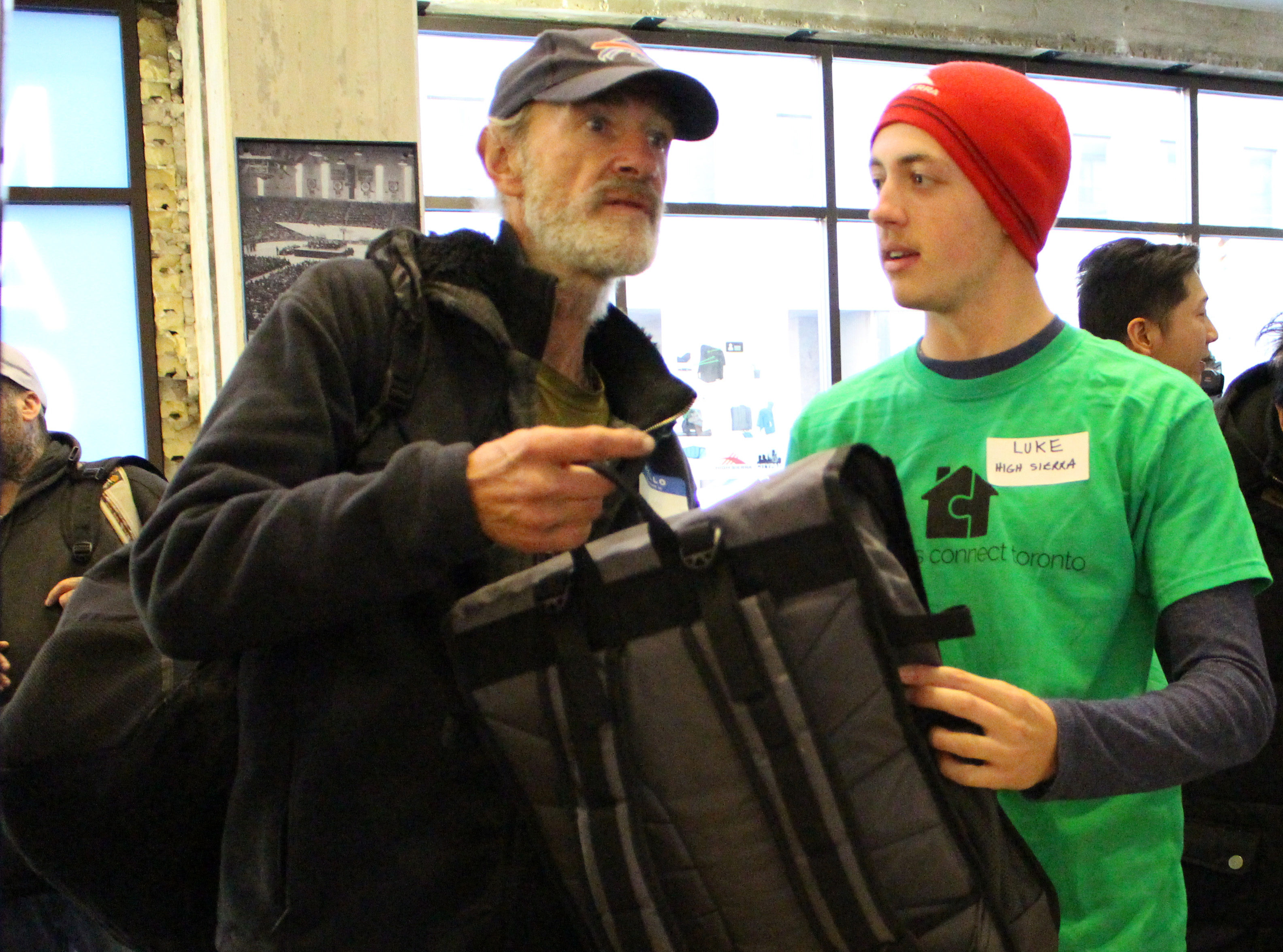 A man receives his new backpack, designed for life on the streets. (Robert Liwanag/Ryersonian Staff)