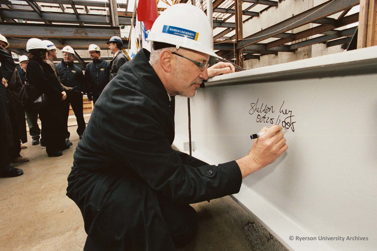 Ryerson president Sheldon Levy signs his name and dates a structural steel beam on Oct. 25, 2005 during construction at the Ted Rogers School of Management west of Yonge Street. (Courtesy Ryerson Archives)