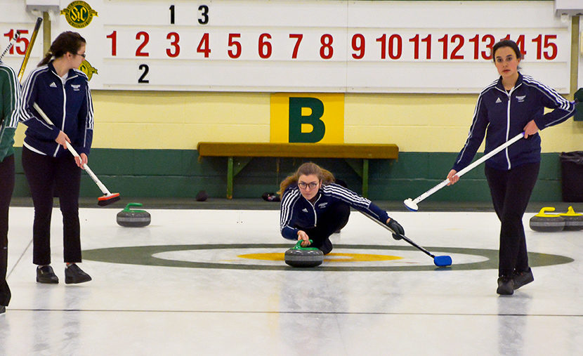 Women's team skip Maggie Macintosh (middle) lines up a rock. Photo courtesy Ryerson Curling Team.