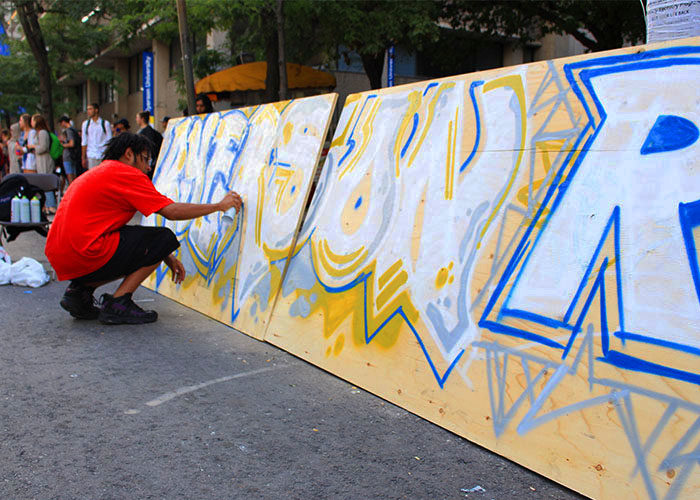 Gene One creates the outline for his graffiti installation.