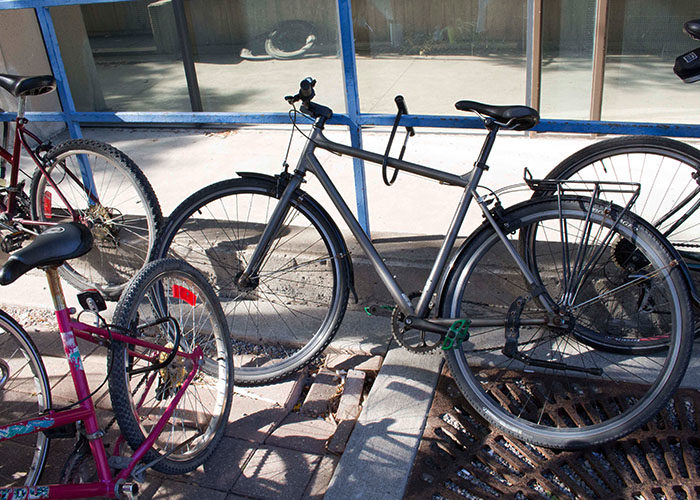 Several bikes are chained to a railing outside a campus building.