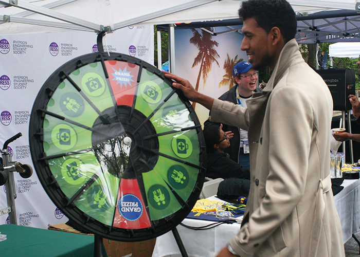 Sponsor Manulife Financial had a Wheel of Fortune-style spinning wheel to draw in crowds. Prizes included lanyards, toothbrushes and earbuds. Biomedical Science student Imaad Hamud gives it a spin. (Brooks Harvey)