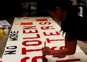 Phyllis McKenna painting a banner for the vigil. (Mallory Warren)