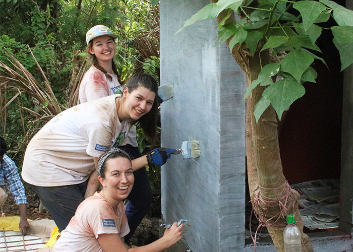 Ryerson volunteers paint a newly built latrine in India.(Courtesy Mallory Warren)