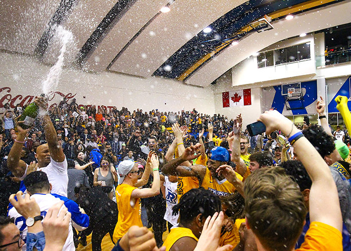 Ryerson players and fans celebrate after the men's basketball team defeated the Carleton Ravens 73-68 to capture the Wilson Cup, the first OUA Championship in school history. This photo, taken on March 12, 2016, was awarded the 2015-2016 OUA Photo of the Year. (Courtesy Alex D'Addese)