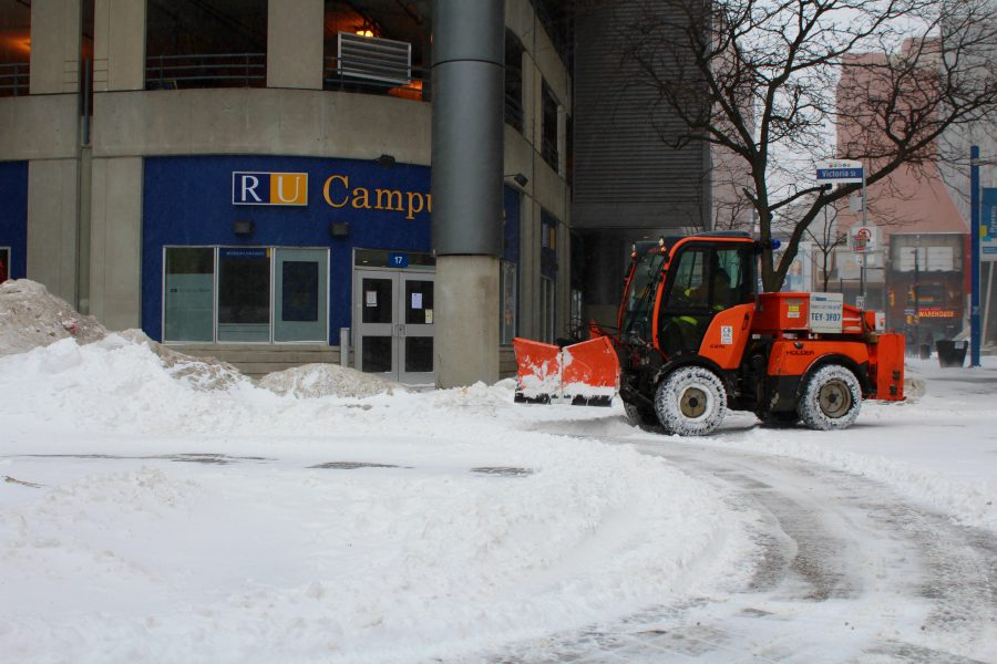 Snow plow clearing streets on campus