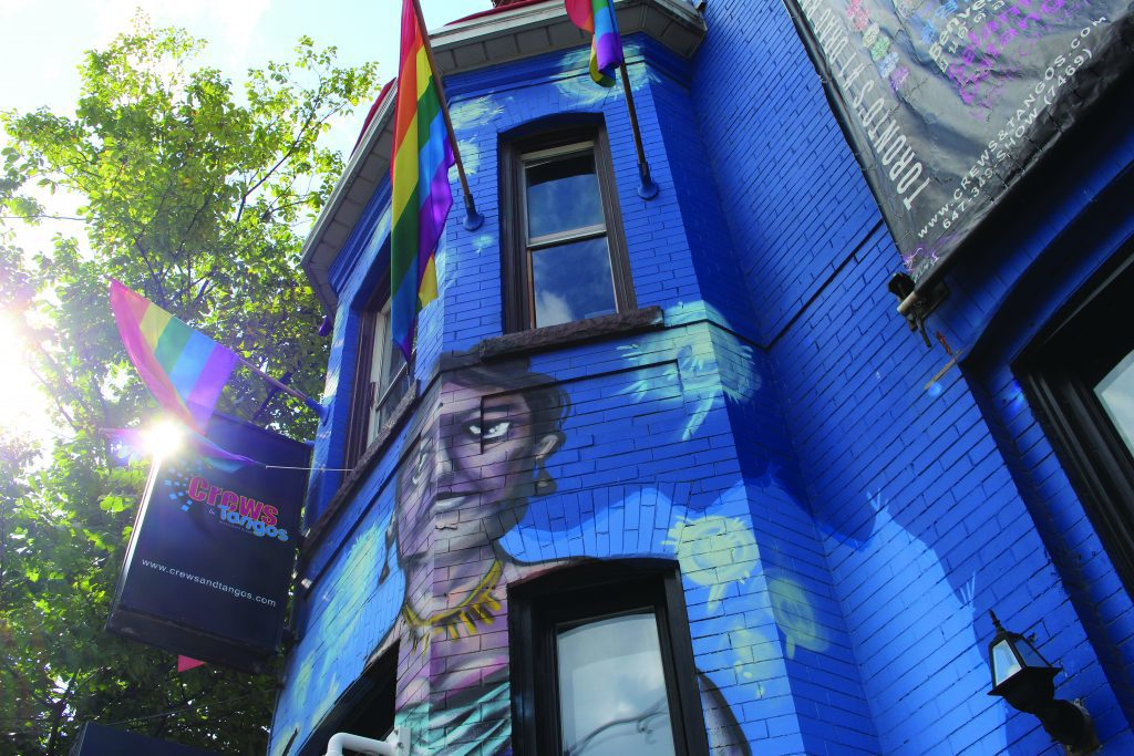 Blue brick building with painting of woman and rainbow flags hanging
