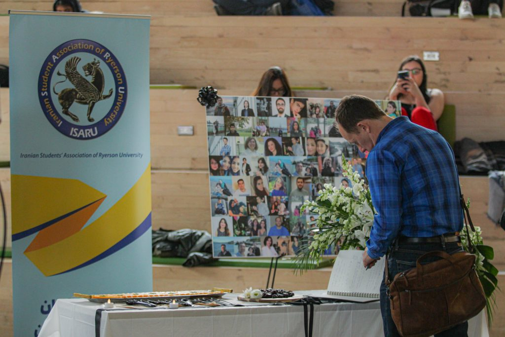 A man stands in front of a table with a sign reading Iranian Student Association of Ryerson University and a board with photos on it