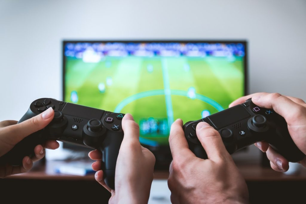 two hands with controllers playing a soccer video game on a television set in front of them
