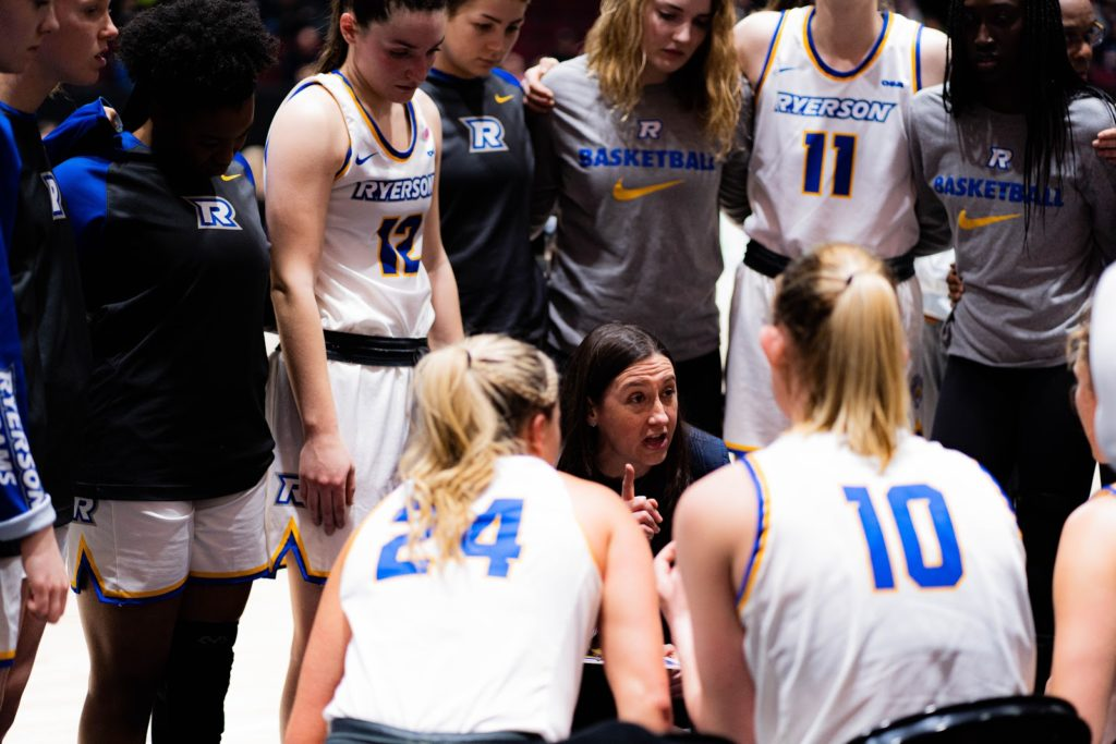 a team of players on a women's basketball team huddle together around their coach