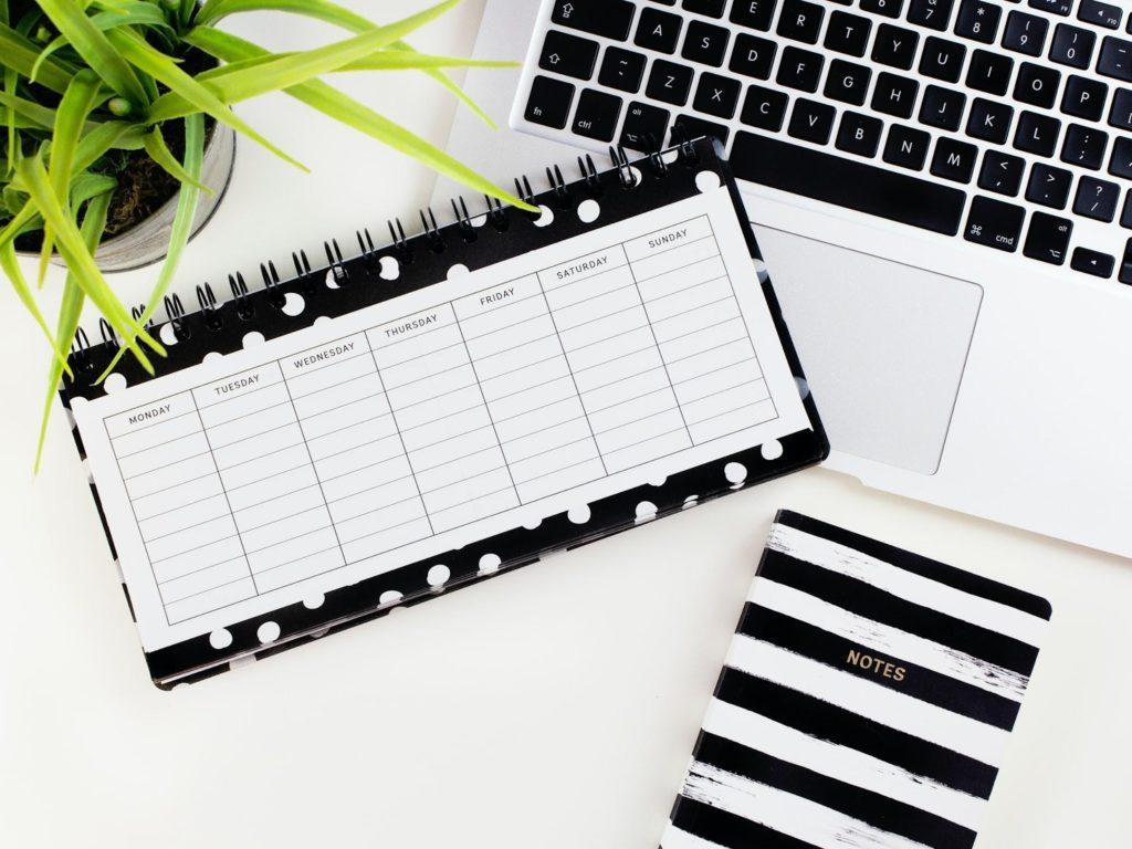 a miniature planner on a macbook laptop keyboard