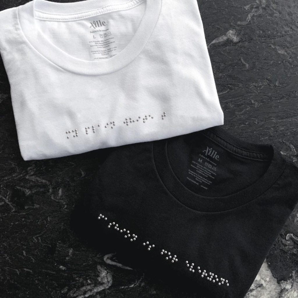 two shirts, one black and one white with crystals that act as Braille