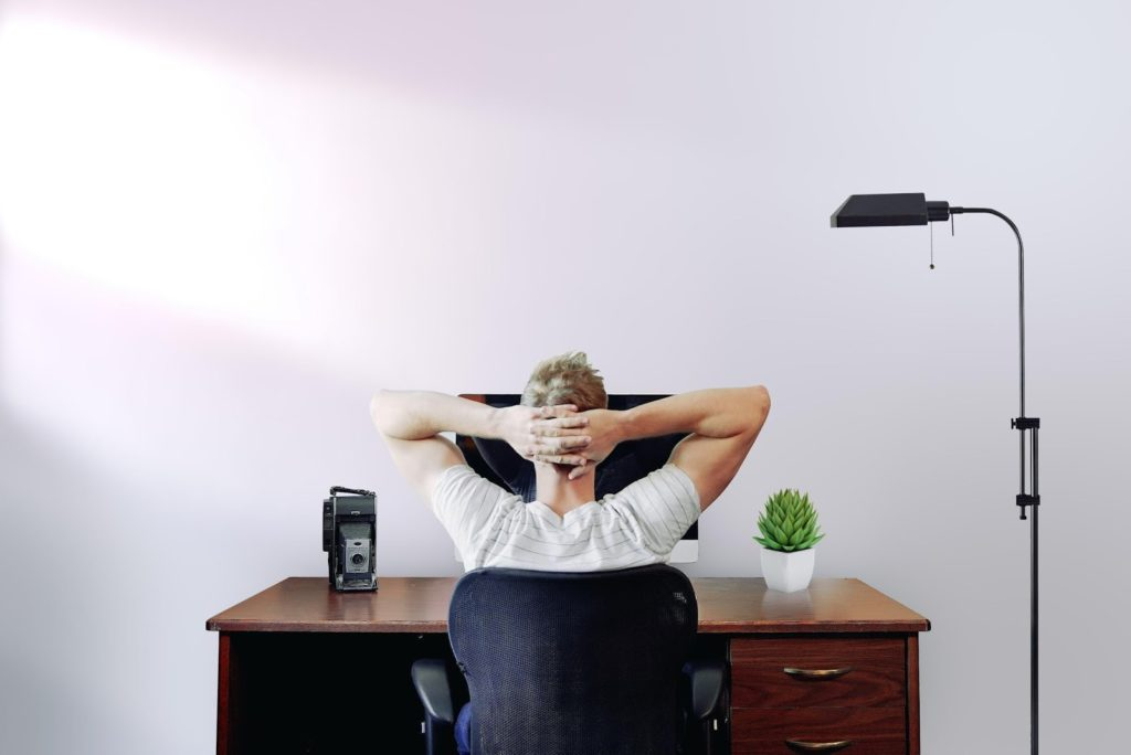 a person stares at a blank wall with their arms folded on their head at their desk