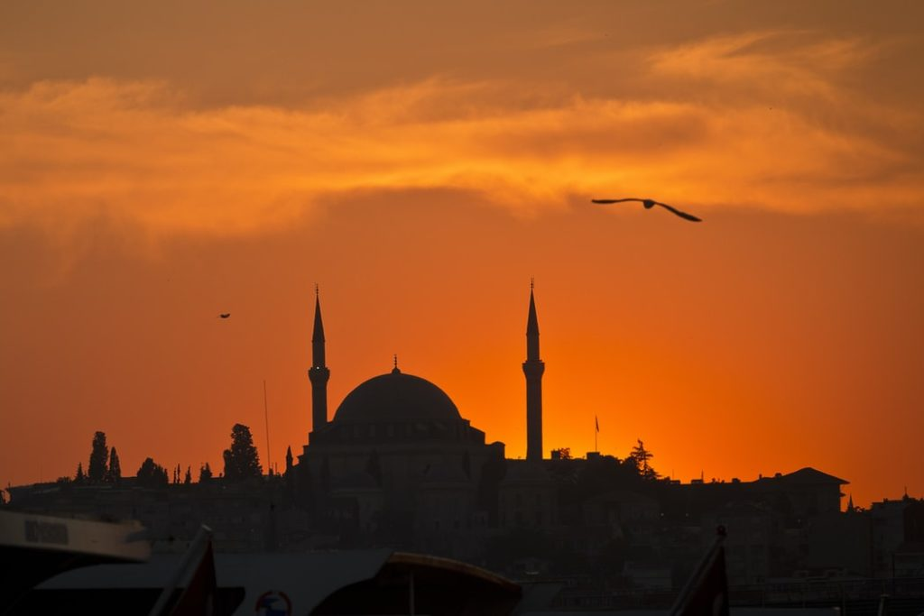 A silhouette of a mosque in the evening with a bird flying in the sky
