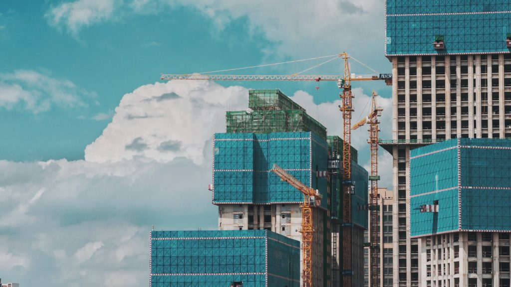 a shot of buildings under construction with a large crane in their midst